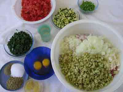 Adding more ingredients for greek recipe keftedes kalokairinoi summer meatballs.