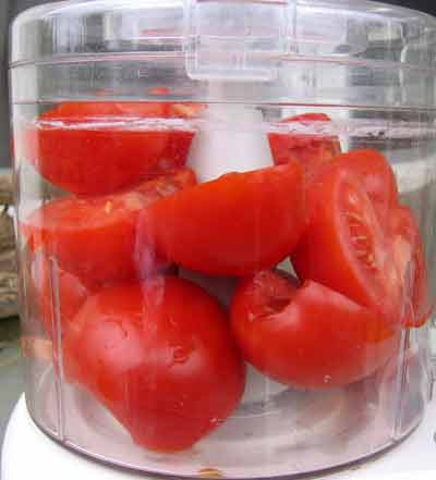 Tomatoes in food processor, ready to puree.
